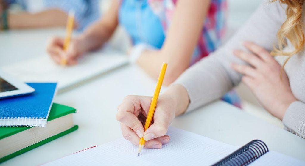 יד כותבת על מחברת בתוך כיתה