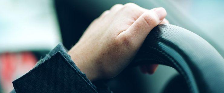 יד נשית אוחזת בהגה מכונית