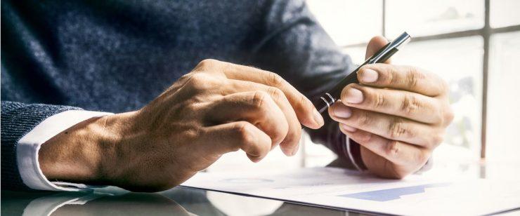 יד אוחזת בעט מעל גיליון נייר