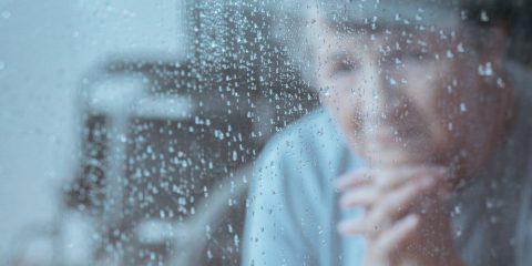 אישה מבוגרת משלבת את כפות ידיה ובוהה בקיר זכוכית רטוב