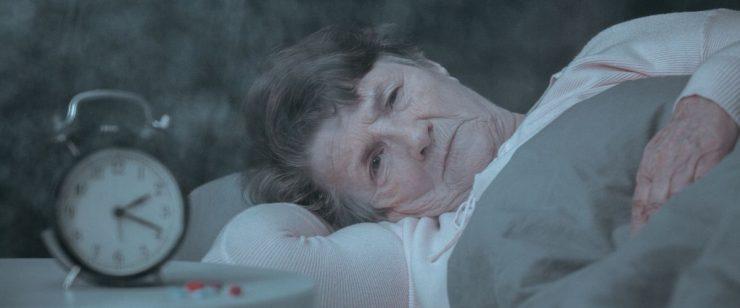אישה מבוגרת שוכבת ובוהה על המיטה