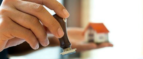 יד אוחזת בחותמת על רקע מודל של בית