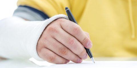 אדם כותב עם יד מגובסת