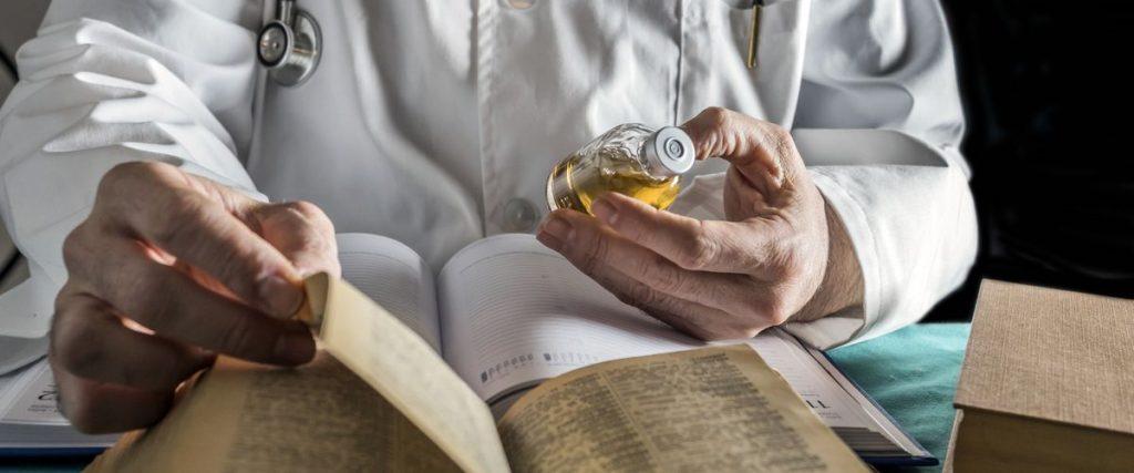 רופא מחזיק תרופה וקורא בספר