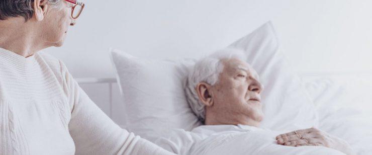 אישה אוחזת בידו של גבר תשוש נפש במיטתו